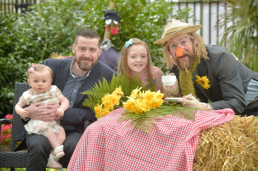 Councillor Matt Garrett, Chair of the People and Communities Committee,  enjoys tea with nine-month old Maisie McErlean, her sister Ella and Paul the scarecrow as they launch the Spring Fair that takes place at Barnett Demesne on Saturday/Sunday 29-30 April between 1.30pm-5.30pm.