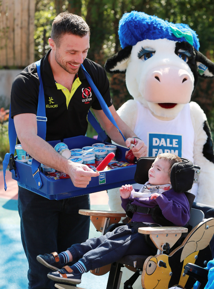 Ulster Rugby player, Tommy Bowe, joins Eoin (3) from Lisburn in the garden of the Mencap Children's Centre for a Dale Farm ice-lolly.
