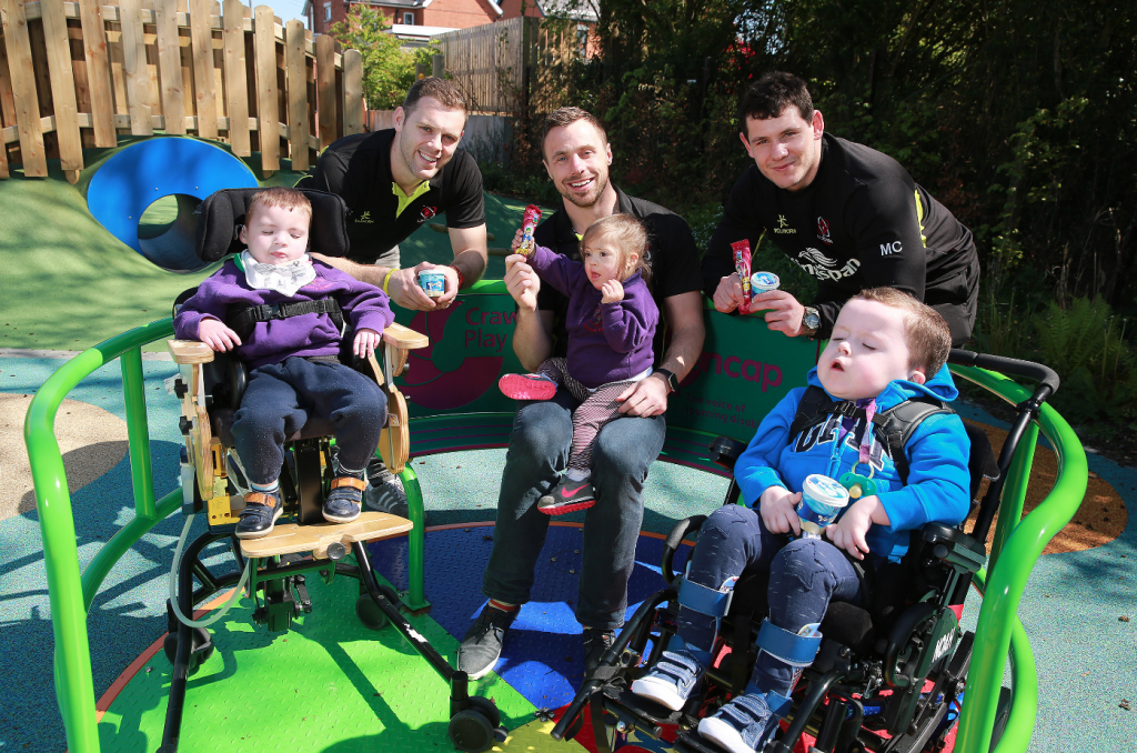 L-R - Ulster Rugby players Darren Cave, Tommy Bowe and Marcell Coetzee join Eoin (3, Lisburn), Lauren (3, Lisburn) and Noah (3, Lisburn) on the roundabout in the Mencap Children's Centre garden for a special ice-cream delivery